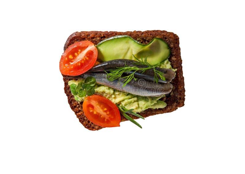 Brinde ou sanduíche no tommy marrom - pão com os tomates sem sementes do abacate, da anchova e de cereja isolados no fundo branco imagens de stock royalty free
