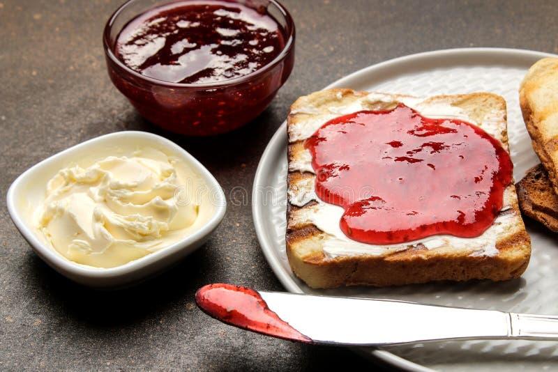 Brindes com atolamento brinde friável fritado com doce vermelho em um fundo escuro Close-up do pequeno almoço fotos de stock