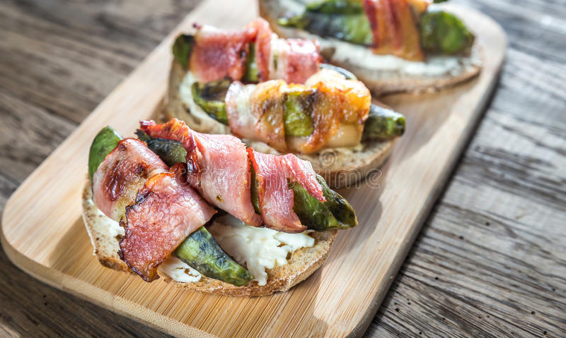 Brindes com o queijo creme e o abacate envolvidos no bacon fotografia de stock