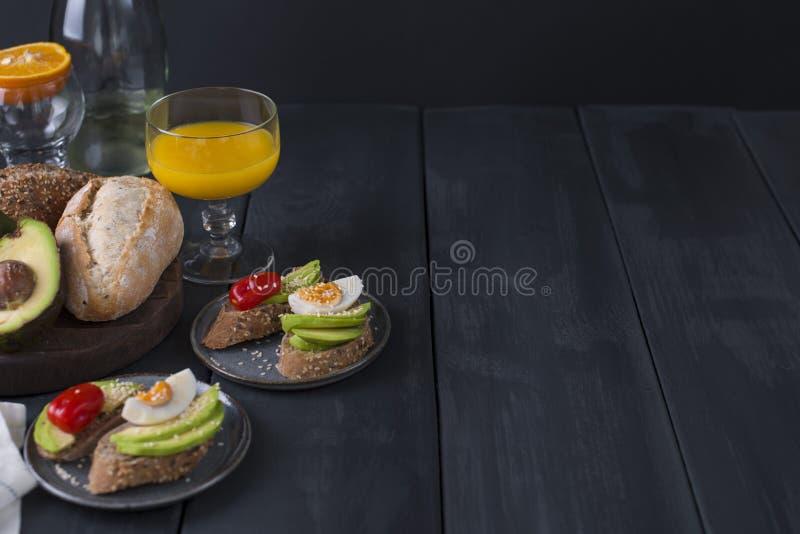 Brindes com os tomates do abacate, do ovo e de cereja, em um fundo de madeira preto Suco e vinho branco, alimento delicioso para  imagens de stock