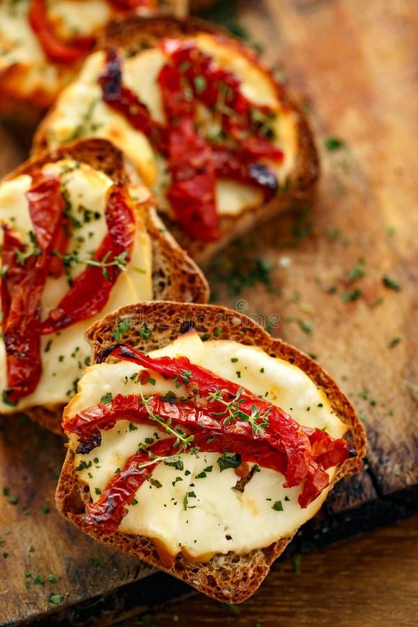 Brindes com queijo fumado do leite de carneiros, os tomates sol-secados e as ervas fotos de stock royalty free