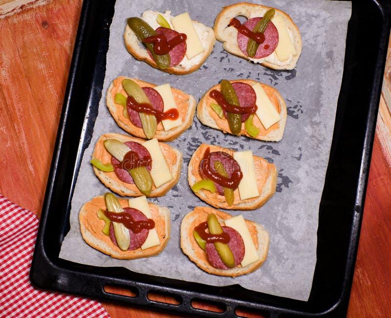 Brindes com salame, ketchup, queijo e pepino em uma placa pronta para ser cozido no forno fotografia de stock royalty free