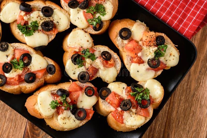 Brindes cozidos com mozarella, tomates, azeitonas e alho fotos de stock