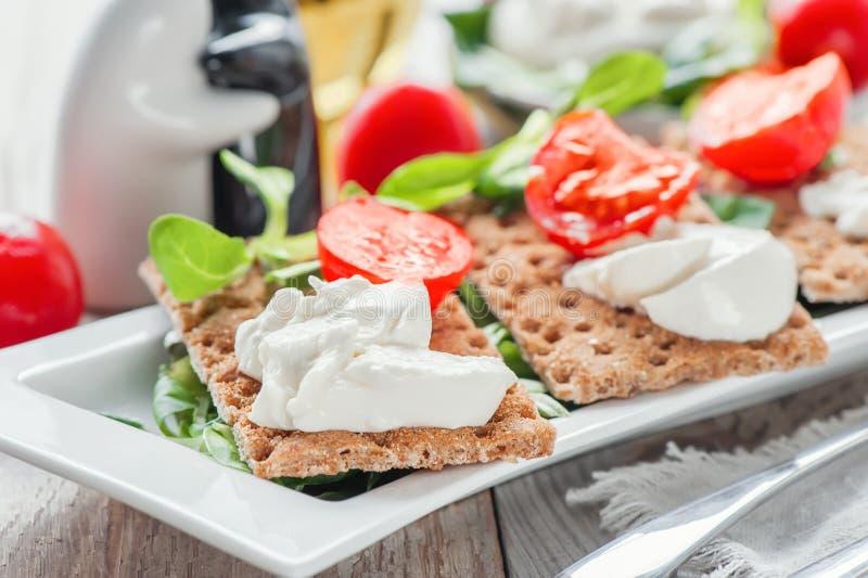 Brindes do queijo de Burato com tomates e salada verde em uma placa branca O conceito de comer saudável imagens de stock royalty free
