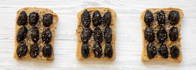 Brindes do vegetariano com manteiga de amendoim, azeitonas e sementes do chia em uma superf?cie de madeira branca, vista superior fotografia de stock royalty free