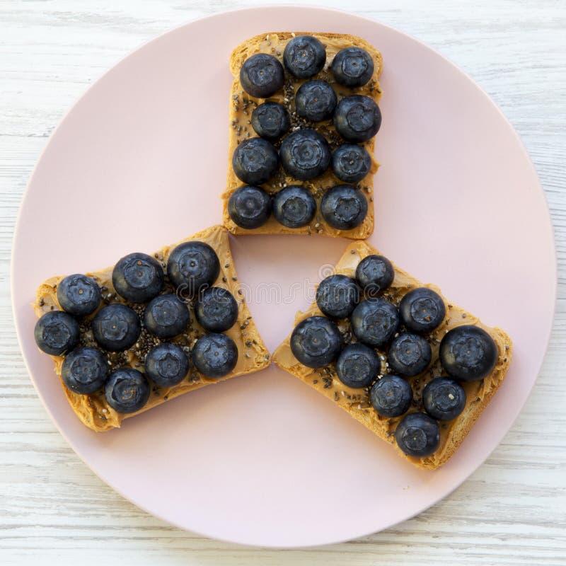 Brindes do vegetariano com manteiga de amendoim, mirtilos e sementes do chia em uma placa cor-de-rosa sobre a superf?cie de madei fotografia de stock