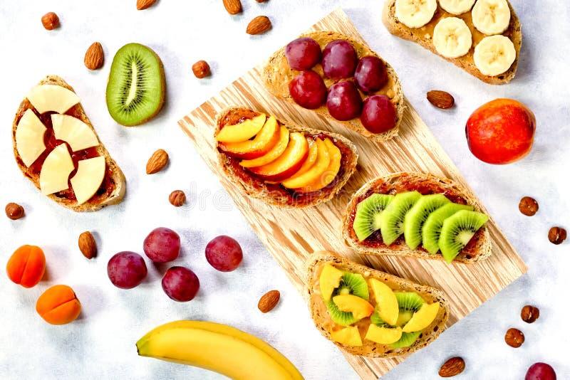 Brindes doces do café da manhã com manteiga de amendoim, doce de morango, banana, uvas, pêssego, quivi, abacaxi, porcas Copie o e fotos de stock royalty free