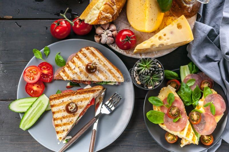 Brindes fumados da carne, tomates, queijo branco e espinafres Close-up Vista superior imagem de stock