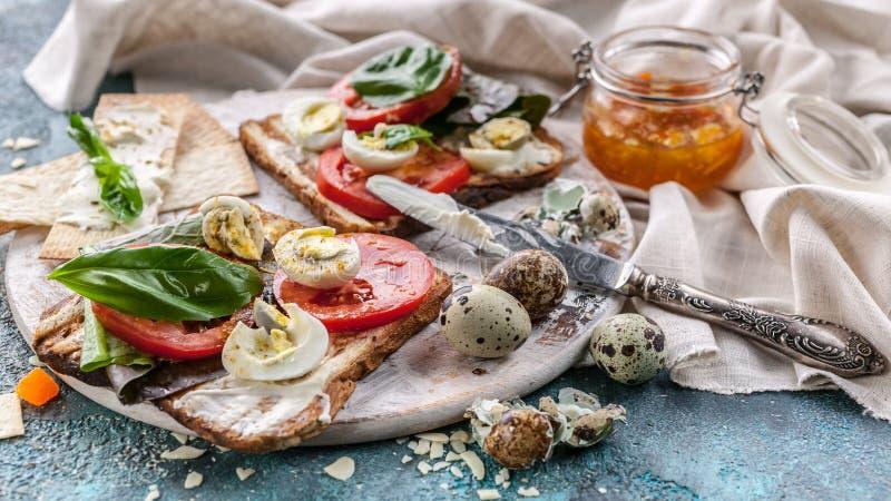 Brindes italianos com queijo, tomates da bandeira do alimento, manjericão, ovos de codorniz Ideias para um café da manhã saboroso foto de stock