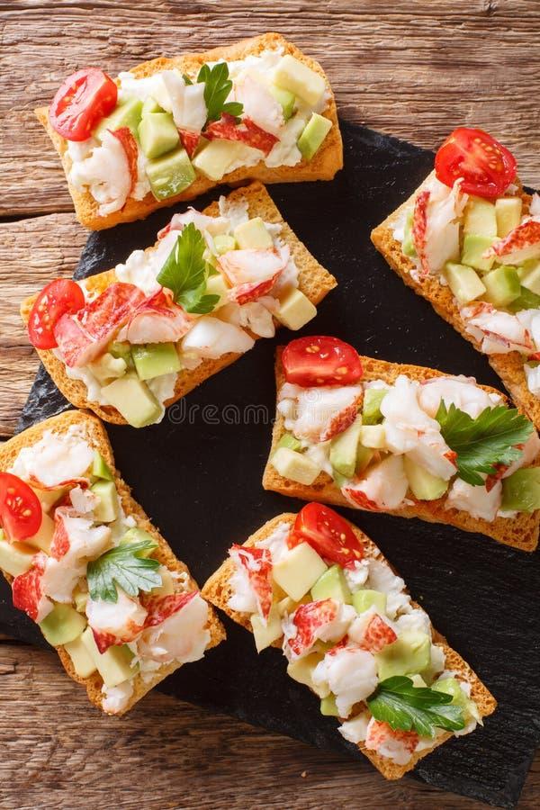 Brindes saborosos com os clos da lagosta, do abacate, do tomate e do queijo creme imagens de stock royalty free