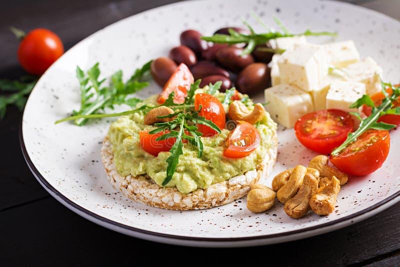 Brindes saudáveis do abacate para o café da manhã ou o almoço, abacate do guacamole, azeitonas de kalamata foto de stock