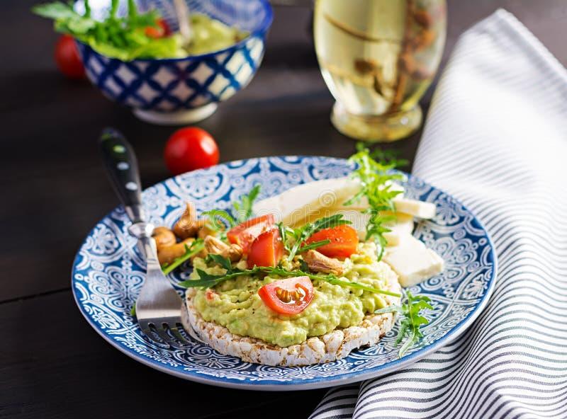Brindes saudáveis do abacate para o café da manhã ou o almoço, abacate, rúcula, tomates fotos de stock royalty free
