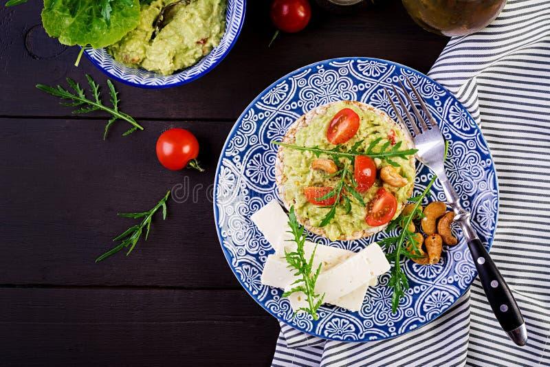 Brindes saudáveis do abacate para o café da manhã ou o almoço, abacate, rúcula, tomates foto de stock royalty free