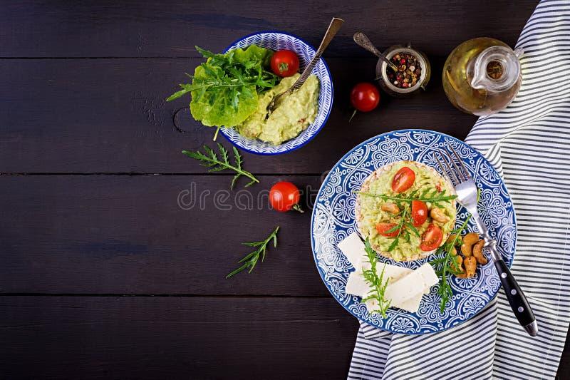 Brindes saudáveis do abacate para o café da manhã ou o almoço, abacate, rúcula, tomates imagem de stock royalty free