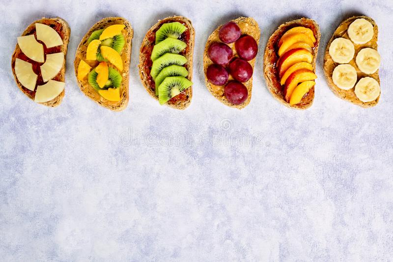 Brindes saudáveis do café da manhã com manteiga de amendoim, doce de morango, banana, uvas, pêssego, quivi, abacaxi, porcas Copie fotos de stock royalty free