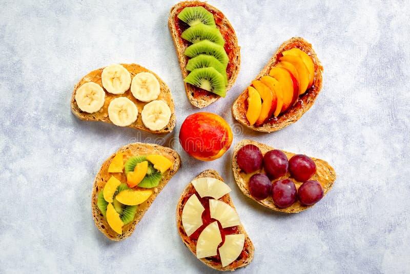 Brindes saudáveis do café da manhã com manteiga de amendoim, doce de morango, banana, uvas, pêssego, quivi, abacaxi, porcas Copie fotografia de stock