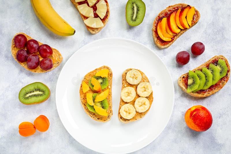 Brindes saudáveis do café da manhã com manteiga de amendoim, doce de morango, banana, uvas, pêssego, quivi, abacaxi, porcas Copie fotografia de stock royalty free