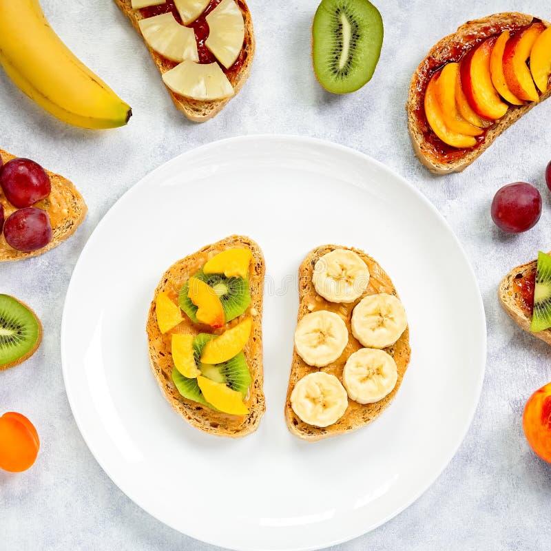 Brindes saudáveis do café da manhã com manteiga de amendoim, doce de morango, banana, uvas, pêssego, quivi, abacaxi, porcas Copie imagem de stock royalty free