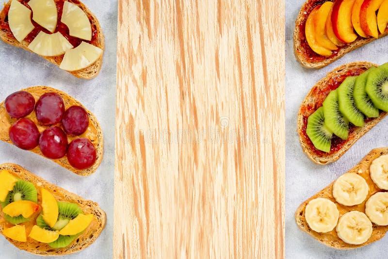Brindes saudáveis do café da manhã com manteiga de amendoim, doce de morango, banana, uvas, pêssego, quivi, abacaxi, porcas Copie imagem de stock