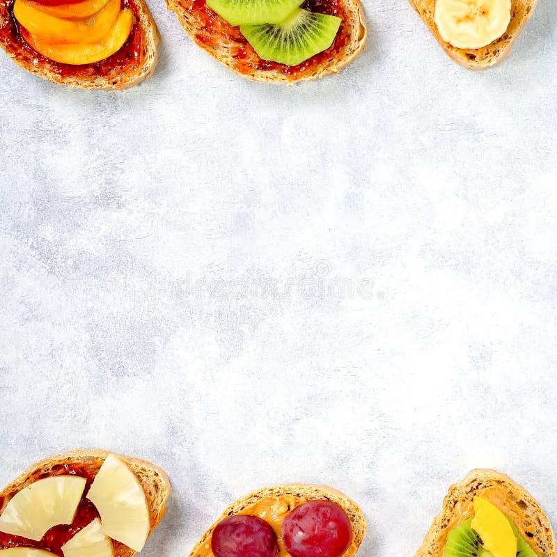 Brindes saudáveis do café da manhã com manteiga de amendoim, doce de morango, banana, uvas, pêssego, quivi, abacaxi, porcas Copie imagens de stock royalty free