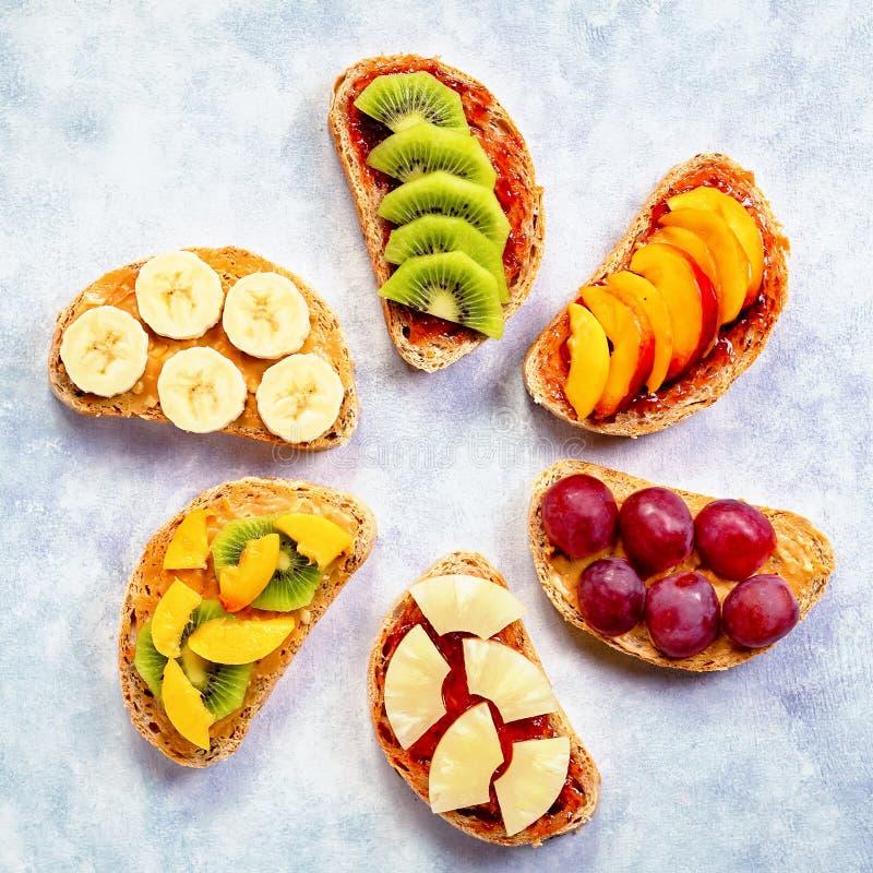 Brindes saudáveis do café da manhã com manteiga de amendoim, doce de morango, banana, uvas, pêssego, quivi, abacaxi, porcas Copie foto de stock royalty free