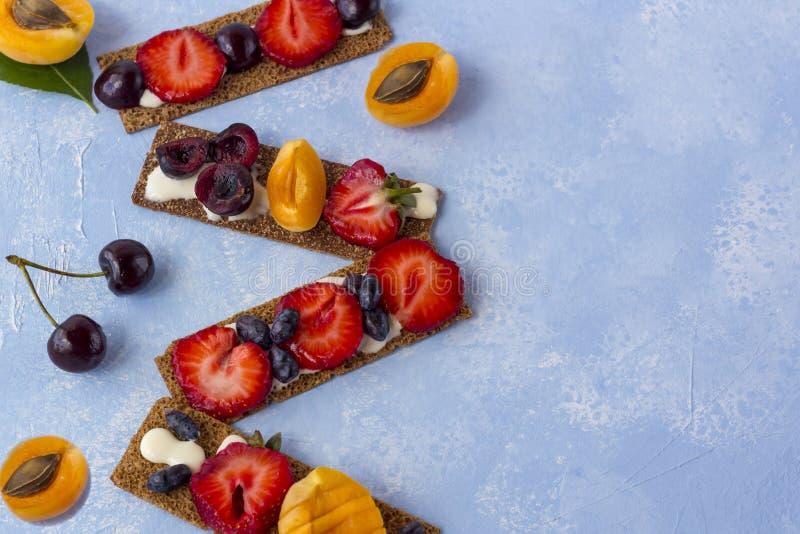 Brindes saudáveis e saborosos com queijo, frutos e bagas de coalho em um fundo azul fotografia de stock royalty free