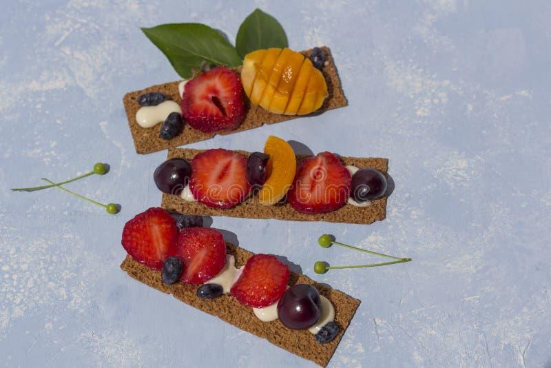 Brindes saudáveis e saborosos com queijo, frutos e bagas de coalho em um fundo azul imagem de stock royalty free