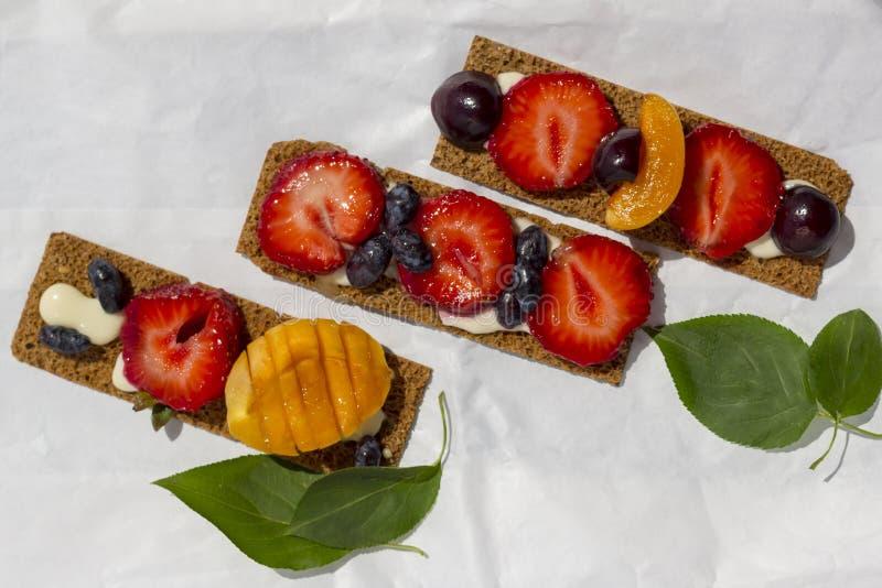 Brindes saudáveis e saborosos com queijo, frutos e bagas de coalho em um papel de pergaminho branco foto de stock royalty free