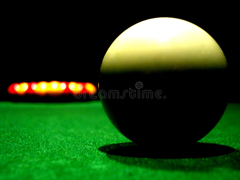 Bring it on. A white pool ball ready to break stock photography