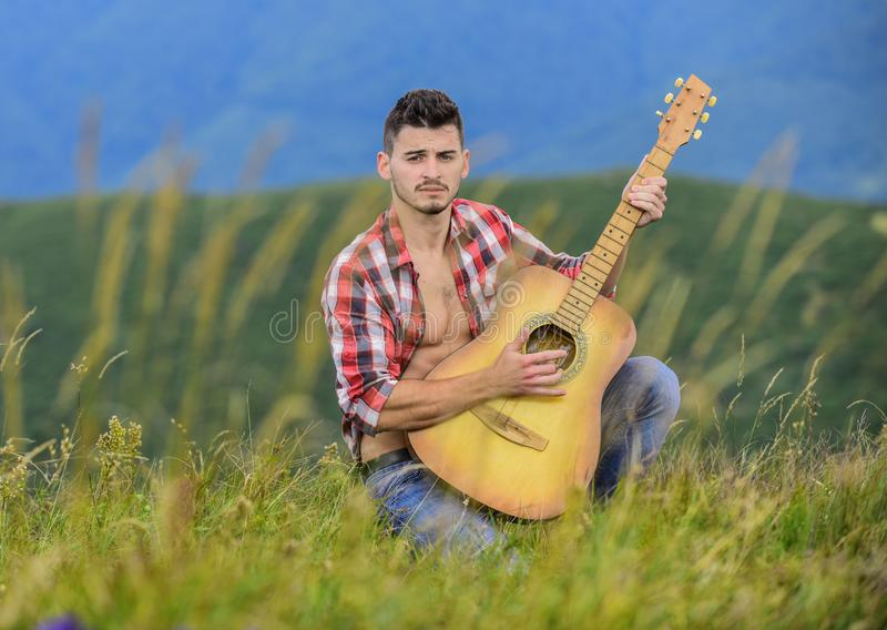 Bring Music to Life. sexy man with guitar in checkered shirt. hipster fashion. western camping and hiking. happy and. Free. cowboy man with acoustic guitar royalty free stock photography