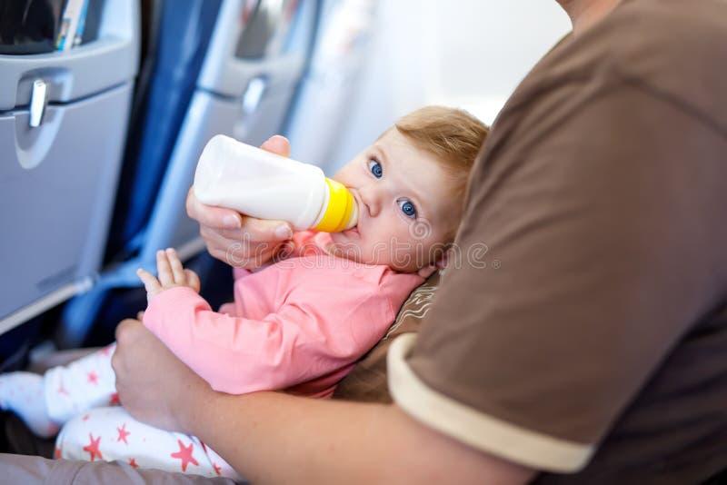 Bringen Sie das Halten seiner Babytochter w?hrend des Fluges auf dem Flugzeug hervor, das auf Ferien geht stockbild