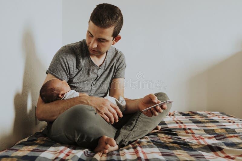 Bringen Sie das Halten seines Babys bei der Anwendung seines Telefons hervor stockbild