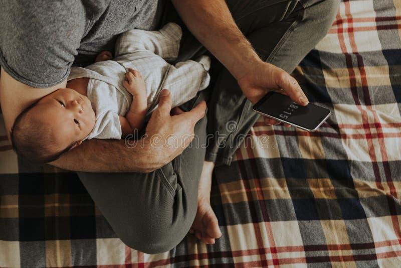 Bringen Sie das Halten seines Babys bei der Anwendung seines Telefons hervor lizenzfreies stockbild