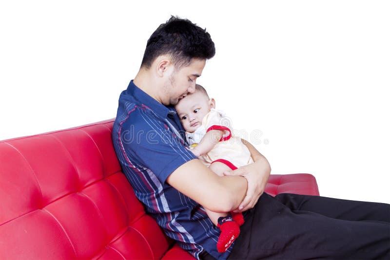 Bringen Sie das Halten seines kleinen Sohns auf dem Sofa hervor lizenzfreie stockbilder
