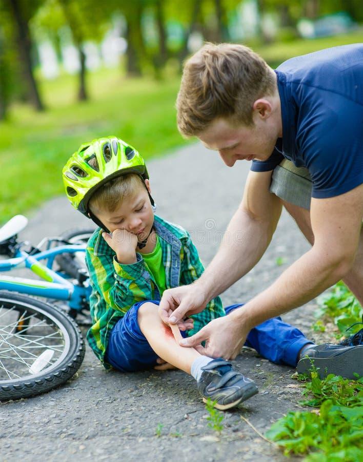 Bringen Sie das Setzen des Pflasters auf die Verletzung des Jungen hervor, die weg von seinem Fahrrad fiel stockfotos