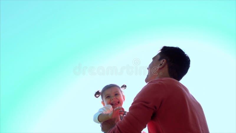 Bringen Sie das Spielen mit dem Tochtermädchen hervor, das in die Luft wirft clip Glückliches aktives Kinderkind Vater wirft sein lizenzfreie stockbilder