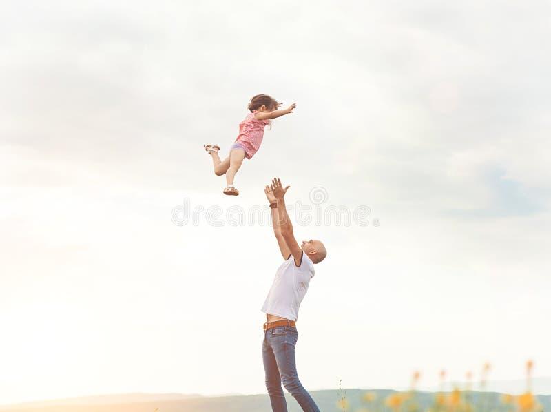 Bringen Sie das Spielen mit seiner Tochter auf dem sonnigen Gebiet hervor stockbilder