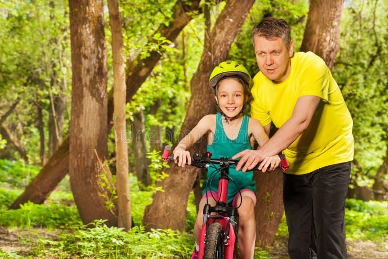 Bringen Sie das Unterrichten seiner Tochter hervor, Fahrrad zu fahren stockfotografie