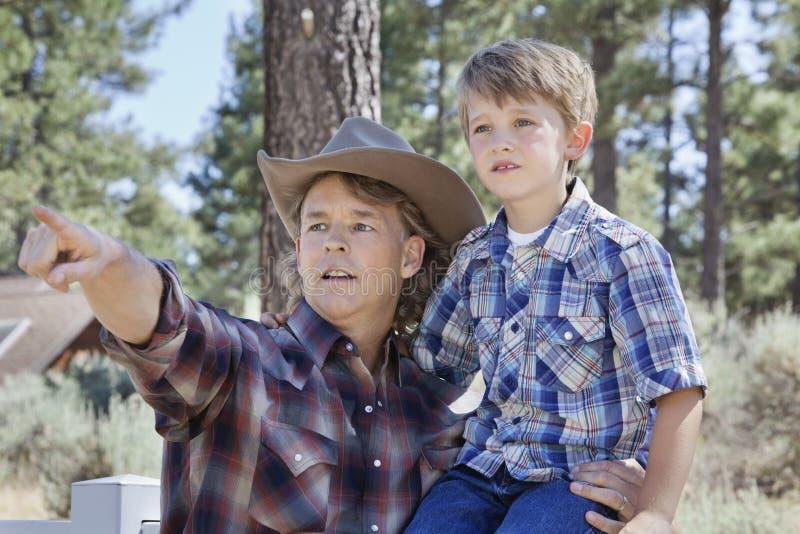 Bringen Sie das Unterstreichen an etwas zu seinem Sohn im Park hervor stockfotos