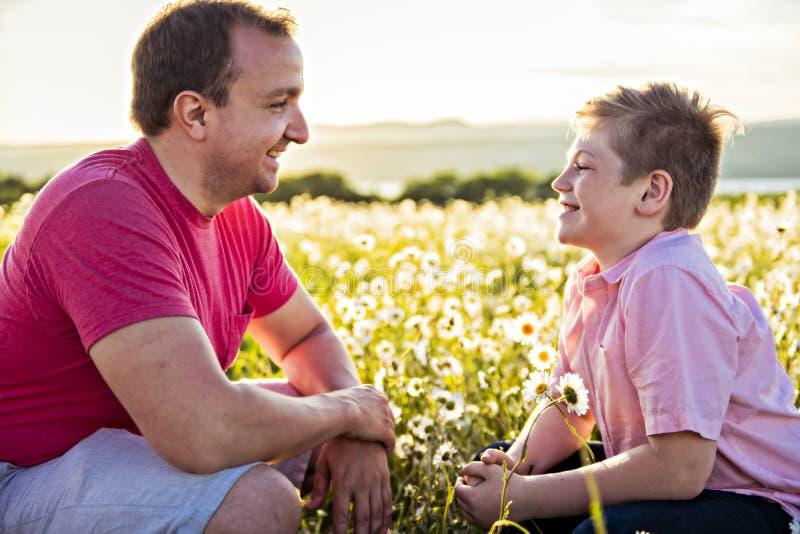 Bringen Sie das Verbringen von Zeit mit Sohn während des Sonnenuntergangs hervor lizenzfreies stockfoto