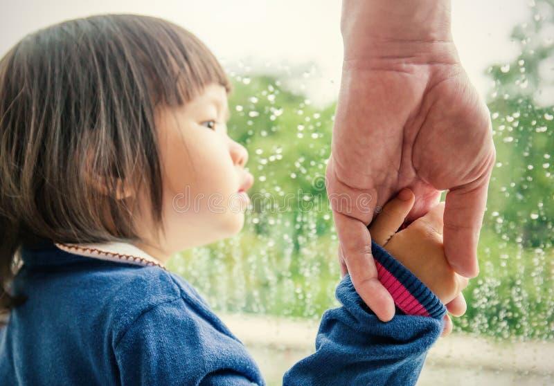 Bringen Sie die Hand hervor, die seine Tochterhand hält, die außerhalb des Fensters schaut lizenzfreies stockbild
