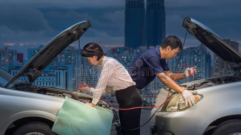 Bringen Sie eine Autobatterie unter Verwendung der Kabel auf Straße herein in die Stadt in Schwung stockbild