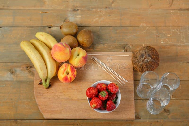 Bringen Sie für Fruchtcocktail auf einer Schneidebretterdbeere, Pfirsiche, Kiwi, Kokosnuss unter lizenzfreie stockbilder