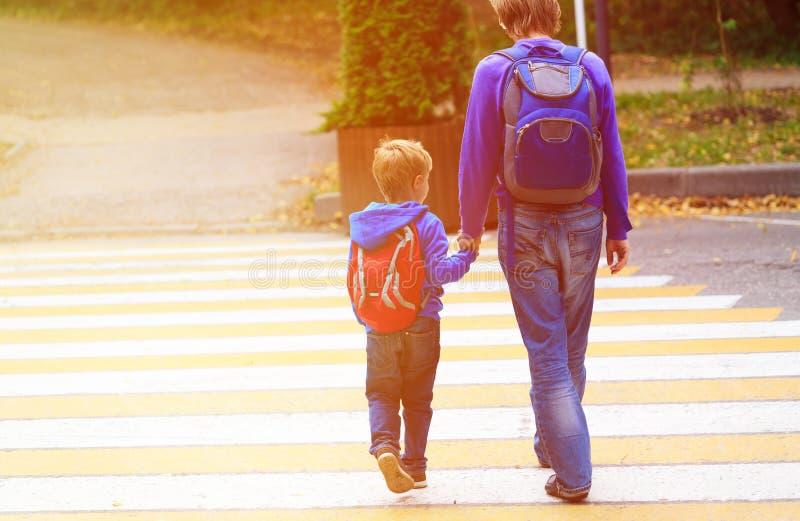 Bringen Sie gehenden kleinen Sohn zur Schule oder zum Kindertagesstätte hervor lizenzfreie stockfotografie