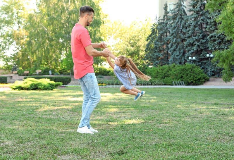 Bringen Sie Haben des Spaßes mit seinem netten Kind im grünen Park am sonnigen Tag hervor stockfotos
