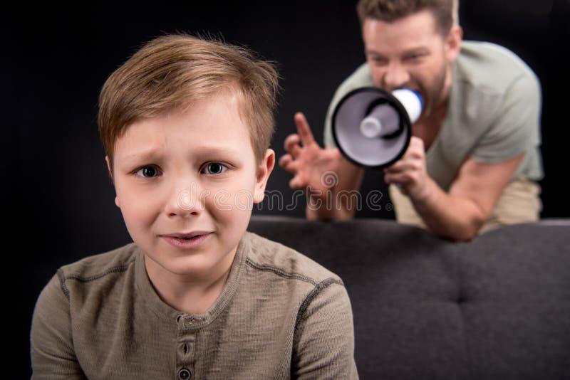 Bringen Sie mit dem Megaphon hervor, das an erschrockenem kleinem Sohn schreit stockbild