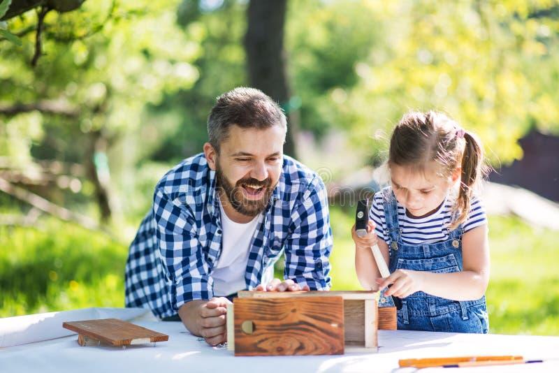 Bringen Sie mit einer kleinen Tochter draußen hervor und hölzernes Vogelhaus machen lizenzfreie stockfotografie
