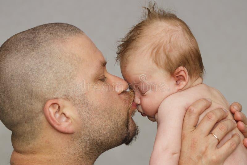 Bringen Sie mit seinem jungen Baby hervor, das ihn auf Backe streichelt und k?sst Elternschaft, Liebe lizenzfreies stockfoto