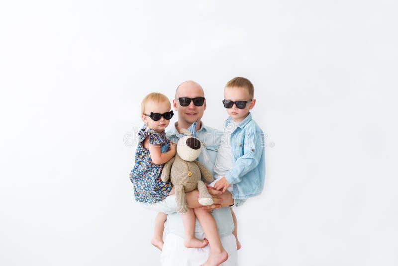 Bringen Sie mit seinen zwei Kindern in den schwarzen Gläsern hervor, welche die Kamera betrachten Auf Weiß stockfotos