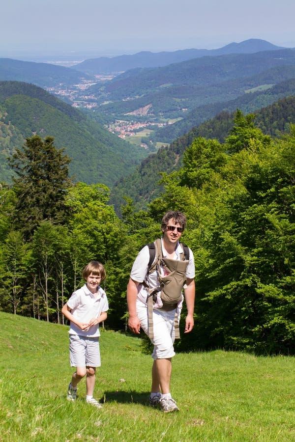 Bringen Sie mit Sohn und neugeborener Tochter in einer Babytrage hervor, die in den Bergen wandert lizenzfreies stockbild